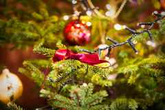 Christmas Decorations Scene. Decorated Christmas Tree with lights and red bow Royalty Free Stock Photo