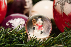 Christmas decorations. Shiny magical crystal ball with snowman and Christmas balls on tree twig. Snowing dome with xmas background Royalty Free Stock Image