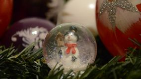 Christmas decorations. Shiny magical crystal ball with snowman and Christmas balls on tree twig. Snowing dome with xmas background.  stock footage