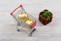 Christmas decorations in a shopping cart on white wooden background Stock Image