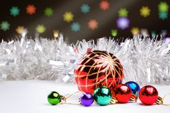 Christmas decorations and silver defocused tinsel on a dark background with blurred lights Stock Photo
