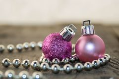 Christmas decorations, silver and pink. Christmas decoration with  bright pink balls and silver beads on a wooden surface Stock Photography