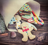 Christmas decorations. Smiling gingerbread men nestled in holiday the background of Christmas decorations. toning image Stock Images