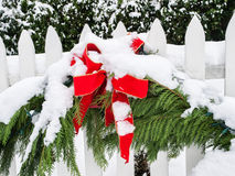 Christmas decorations in snow. Evergreen boughs with red ribbon hanging on white picket fence and covered with snow Stock Photography