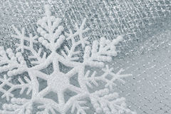 Christmas decorations - snowflake. Christmas decorations -  toy   white snowflake on silver material net Stock Image