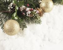 Christmas decorations nestled in snow. Christmas decorations and snowy fir tree branch nestled in snow Royalty Free Stock Photography