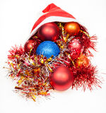 Christmas decorations spill out from red santa hat Stock Photos