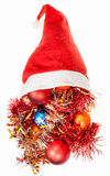 Christmas decorations spill over red santa hat Stock Photography