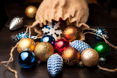 Christmas decorations spilled from canvas bag on a table. Christmas decorations spilled from a full canvas bag on a wooden table royalty free stock images