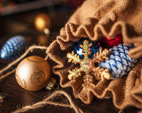 Christmas decorations spilled from canvas bag on a table. Christmas decorations spilled from a full canvas bag on a wooden table stock photo