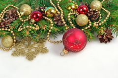 Christmas decorations and spruce branch and cones on a white Royalty Free Stock Images