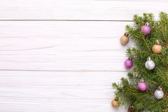 Christmas decorations, on a spruce branch on a white wooden back royalty free stock photo