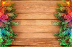 Christmas decorations. With spruce branches and lights at wooden background Royalty Free Stock Photos