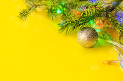 Christmas decorations. With spruce branches and lights on yellow background Royalty Free Stock Photo