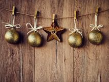 Christmas decorations: Star and golden snowballs on the wooden background. Christmas decorations, toys for the Christmas tree hang royalty free stock image