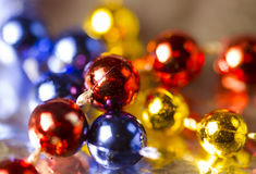 Christmas  decorations. Strings of Sharp Red and sharp and blue beads, glowing yellow beads. Royalty Free Stock Photo