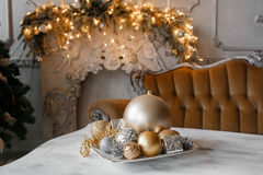 Christmas decorations on the table against the background of a fireplace decorated with branches  spruce and garland. Stock Image