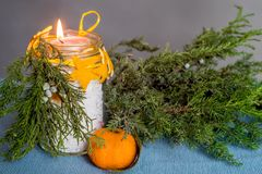 Christmas hand made candle craft on the blue tablecloth with a fir tree spruce and an orange Royalty Free Stock Photo