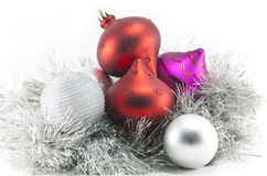 Christmas decorations and tinsel. Colourful red, puprle and silver Christmas / xmas decorations and silver tinsel isolated on white Royalty Free Stock Images