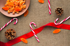 Christmas decorations: top view of candy canes. Christmas decorations: top view composition of candy canes, cones and dried fruits on linen fabric background Stock Image