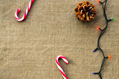 Christmas decorations: top view of candy canes. Christmas decorations: top view composition of candy canes, cones and dried fruits on linen fabric background Royalty Free Stock Photos