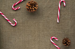 Christmas decorations: top view of candy canes and. Christmas decorations: top view composition of candy canes and cones on linen fabric background Stock Image