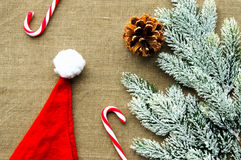 Christmas decorations: top view of candy canes. Xmas decorations: top view of candy canes, cones, Santa hat and pine branch on linen fabric background Stock Photography