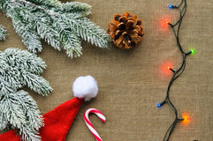 Christmas decorations: top view of candy canes. Xmas decorations: top view of candy canes, cones, Santa hat and pine branch on linen fabric background Royalty Free Stock Images