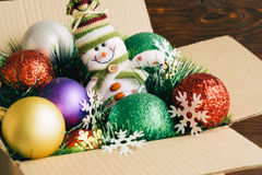 Christmas decorations and toys in a cardboard box on a wooden ba Stock Photo