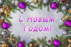 Christmas decorations, toys and spruce branches on grey background. New year`s concept of the Inscription happy New Year.  royalty free stock photography