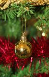 Christmas decorations for tree in gold glitter and red. With sparkles and tinsel Christmas pudding Royalty Free Stock Images