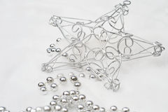 Christmas Decorations. Christmas tree wire star and silver bead garland on the soft cotton Stock Photos