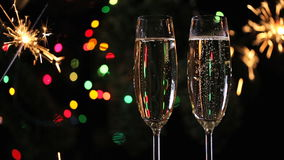 Christmas decorations and two champagne glasses. On bright background and bengal lights stock video