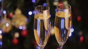 Christmas decorations and two champagne glasses, on bright background stock footage