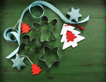 Christmas decorations on vintage green wood background, with cookie cutters. Christmas holiday background with red, white, festive decorations and cookie Royalty Free Stock Photography