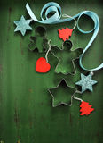 Christmas decorations on vintage green wood background, with cookie cutters - vertical. Stock Images