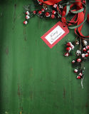 Christmas decorations on vintage green wood background. Vertical with Merry Christmas tag. Christmas holiday background with red, white, festive decorations Royalty Free Stock Photography