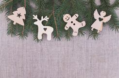 Christmas decorations on the vintage linen backgrounds. Festive winter scenery. Wooden vintage Christmas-tree decorations against the background of spruce twigs royalty free stock image