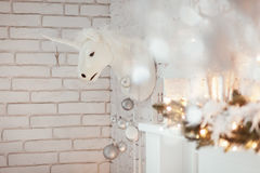 Christmas decorations with white unicorn and candlestick in living room. Burning lantern, xmas tree. Christmas decorations with white unicorn and candlestick in Stock Photography