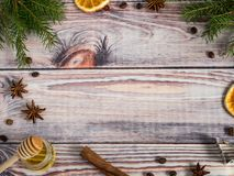 Christmas decorations on wooden background, orange, cinnamon, stars, fir branches. Copy space. Royalty Free Stock Photo