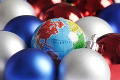 Christmas decorations and world. In between Royalty Free Stock Photo