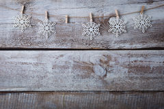 Christmas decorations (snowflake) hanging over wooden background Royalty Free Stock Images