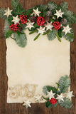 Christmas Decorative Border. Christmas abstract background border with gold glitter joy sign and star decorations,  holly, ivy, mistletoe and snow covered fir on Stock Photos