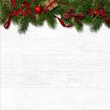 Christmas decorative border with fir branches and red berries on white. Christas decorations with fir branches, berries and a gift on a white wooden background Stock Images