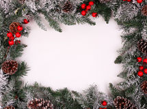 Christmas decorative border with holly berries. Christmas decorative border with pine cones and holly berries over white background royalty free stock photo