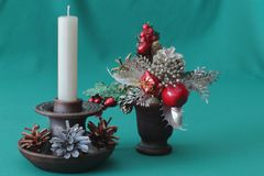 Christmas decorative bouquet in a ceramic vase and ceramic candlestick with a white wax candle and multi-colored pine cones on a royalty free stock images