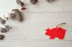 Christmas decorative garland, diagonal to the boards, with red and white berries, snowy fir cones and stars. Top view, flat lay. White woden background stock photography