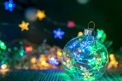 Christmas decorative glass ball against defocused garland lights. Background for new year decor royalty free stock images