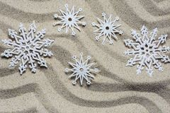 Christmas decorative snowflakes lie on the beach sand stock images