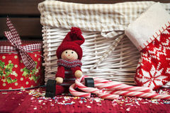 Christmas decorative wooden doll with gift box and xmas sock. Christmas decorative smiling wooden doll with striped candy canes and round gift box and sock on Stock Photo